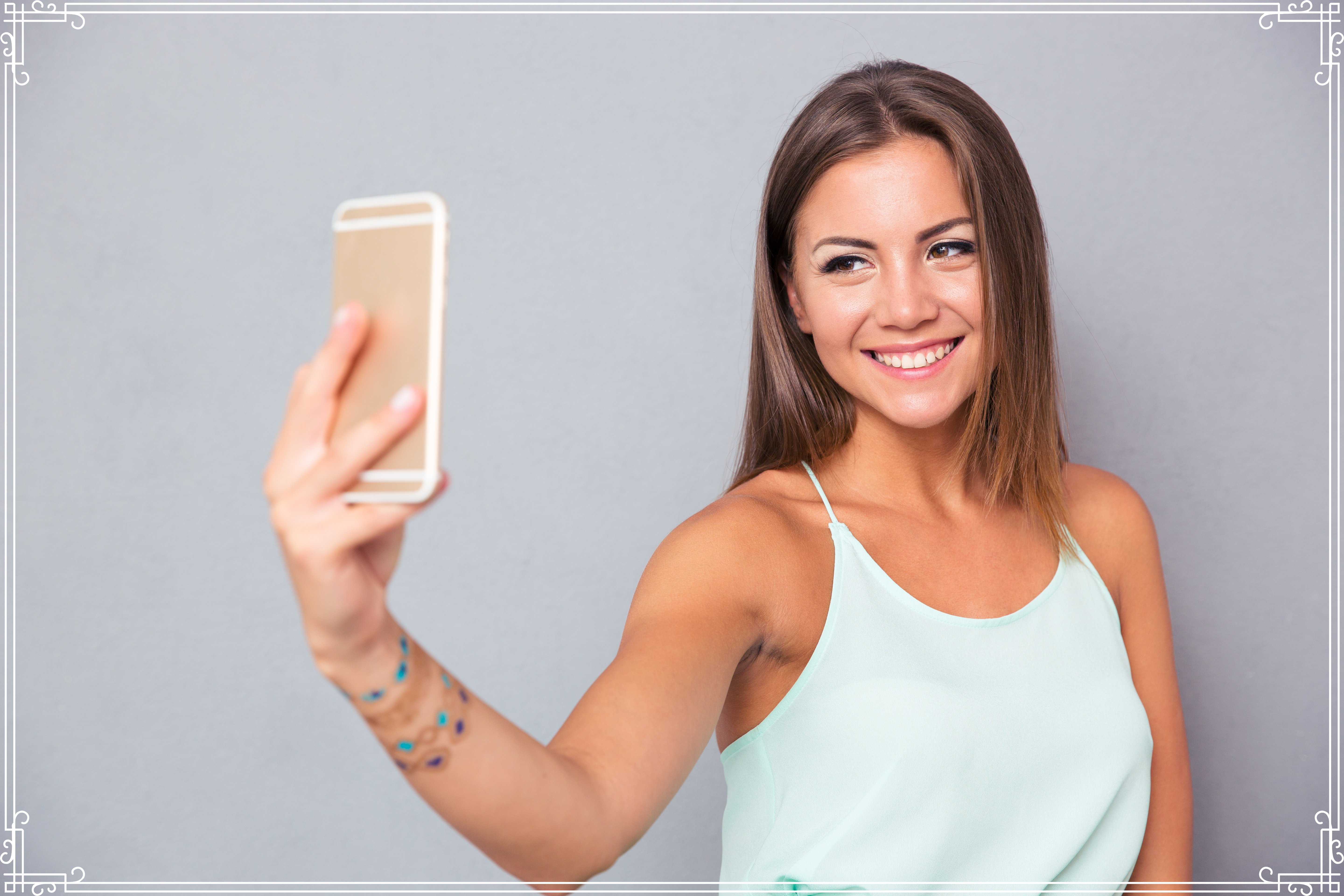 Smiling young girl making selfie photo on smartphone over gray backgro